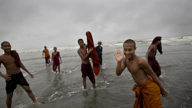 Novice Buddhist monks play in the sea in Sittwe, northwestern Rakhine State, Myanmar, ahead of the arrival of Cyclone Mahasen, Tuesday, May 14, 2013. The U.N. said the cyclone, expected later this week, could swamp makeshift housing camps sheltering tens of thousands of Rohingya. Myanmar state television reported Monday that 5,158 people were relocated from low-lying camps in Rakhine state to safer shelters. But far more people are considered vulnerable. (AP Photo/Gemunu Amarasinghe)