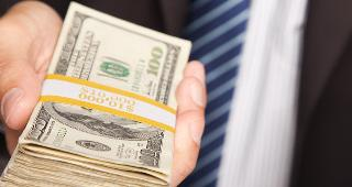 Businessman handing over stack of hundred dollar bills copyright Andy Dean Photography/Shutterstock.com