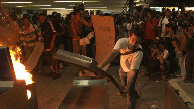 A demonstrator destroys turnstiles during riots at Once railway station in Buenos Aires, Argentina, Friday, Feb. 24, 2012. The discovery of a 51st victim Friday two days after Argentina's deadliest train wreck in decades left the man's family devastated and prompted rock-throwing and other violence by protesters holding vigil at the scene. Riot police responded with tear gas and batons, clearing the station and making arrests.  (AP Photo/Alberto Raggio, DyN)