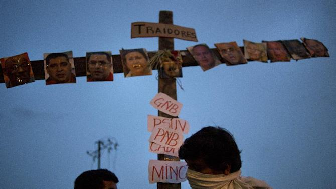 "Anti-government protesters carry a cross covered with photos of government officials and supporters under the Spanish word ""Traitors"" at a demonstration during Holy Week in Caracas, Venezuela, Wednesday, April 16, 2014. The opposition wants President Nicolas Maduro's government to free jailed opponents and create an independent truth commission to determine responsibility for deaths tied to protests that have rocked the nation since February. (AP Photo/Ramon Espinosa)"