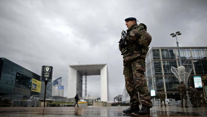 A French soldier patrols near the Arche de la Defense at La Defense business district near Paris