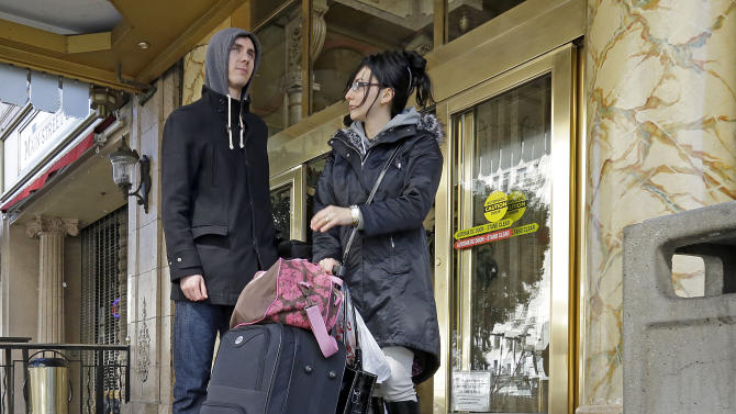 Michael and Sabina Baugh, both 27, of Plymouth, England, wait for transportation as they leave the Cecil Hotel in downtown Los Angeles Wednesday, Feb. 20, 2013. Early Tuesday, police discovered the body of a Canadian woman at the bottom of the historic hotel's water tank, weeks after she was reported missing.  The Baughs, on a 14-day tour package, had been there eight days and had showered in and drank the water. The couple's tour operator was less than cooperative in finding them other accommodations.  (AP Photo/Reed Saxon)