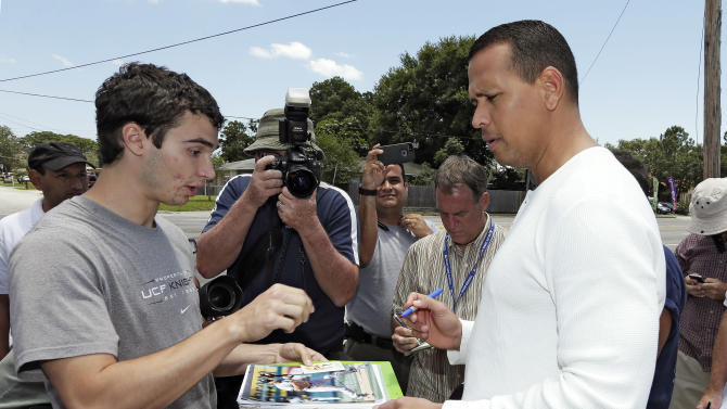 New York Yankees third baseman Alex Rodriguez, right, signs autographs for fans after reporting to the Yankees' Minor League complex for rehabilitation Monday, May 6, 2013, in Tampa, Fla. Rodriguez is getting back on the field for the first time since surgery on his left hip almost four months ago. (AP Photo/Chris O'Meara)