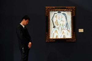 "A man stands beside Picasso's ""Buste de Femme"" at Sotheby's …"