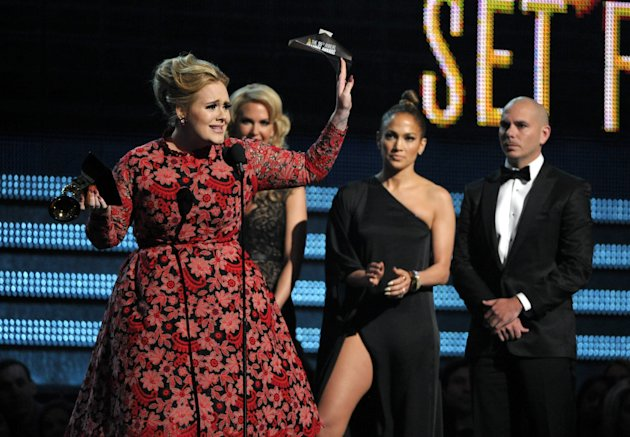 Adele, left, accepts the award for best pop solo performance for &quot;Set Fire to the Rain&quot; at the 55th annual Grammy Awards on Sunday, Feb. 10, 2013, in Los Angeles. Looking on from right are presenters Pitbull and Jennifer Lopez. (Photo by John Shearer/Invision/AP)