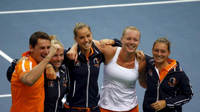 Members of the Netherlands team pose for pictures as they celebrate their victory over Russia in their Fed Cup World Group tennis match in Moscow