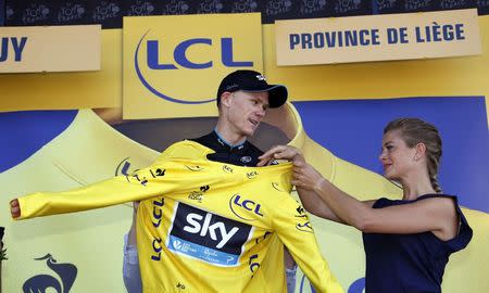 Team Sky rider Chris Froome of Britain celebrates as he wears the race leader's yellow jersey on the podium of the third stage of the 102nd Tour de France cycling race from Anvers to Huy