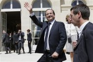 France's President Francois Hollande waves to visitors in the gardens of the Elysee Palace in Paris July 14, 2012. REUTERS/Kenzo Tribouillard/Pool
