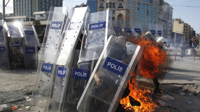 A petrol bomb explodes in front of riot policemen during clashes in Taksim Square in Istanbul, Turkey, Tuesday, June 11, 2013. Hundreds of police in riot gear forced through barricades in Istanbul's central Taksim Square early Tuesday, pushing many of the protesters who had occupied the square for more than a week into a nearby park. (AP Photo/Kostas Tsironis)