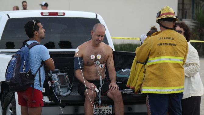 Man is treated by a paramedic after a lightning strike in the water in Venice, California