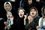 Iranian women cheer as they watch 23 May 2006 members of the national football team training at their camp as they prepare for the World Cup tournament which opens for Iran with a crucial match against Mexico on June 11. Iran is in Group D with Mexico, Portugal and Angola and has chosen the southern German city of Friedrichshafen as their World Cup base. AFP PHOTO/HASSAN AMMAR