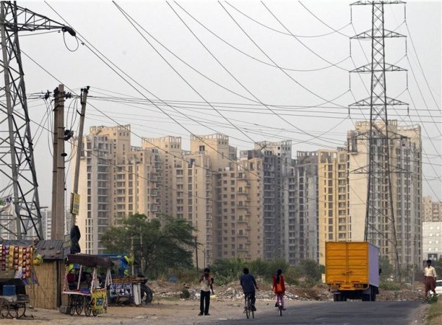 People ride their bicycles under overhead power cables, against the backdrop of multi-story residential apartments at Gurgaon, on the outskirts of New Delhi