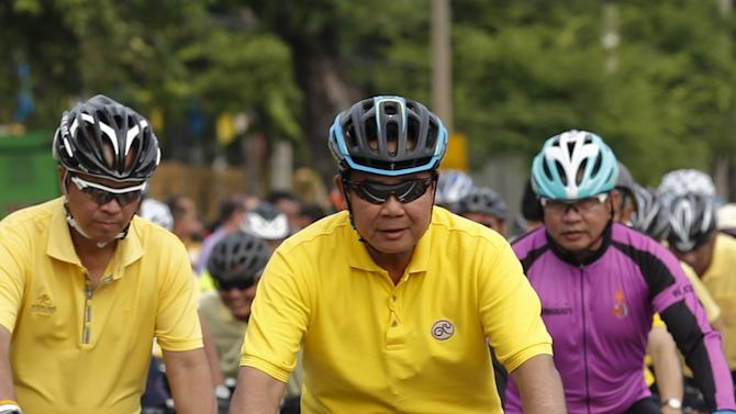 "Thailand's Prime Minister Prayuth Chan-ocha rides a bicycle with his cabinet members and well-wishers during their practice ahead of Thailand's Crown Prince Maha Vajiralongkorn ""Bike for Mom"" campaign in Bangkok"
