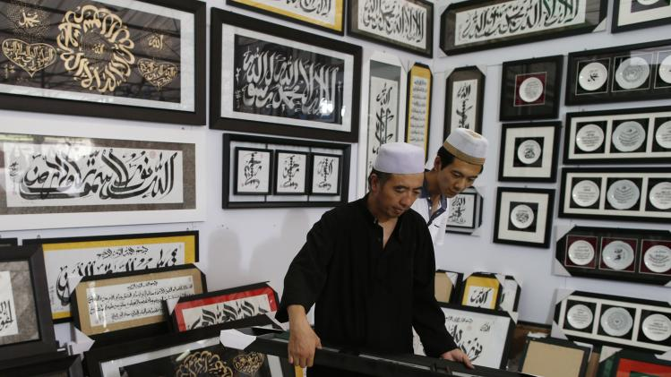 Craftsmen from China prepare to hang a piece of calligraphy work to be sold at a Hari Raya bazaar ahead of Eid al-Fitr in Singapore
