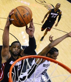Miami Heat guard Dwyane Wade (3) attempts a dunk as San Antonio Spurs forward Kawhi Leonard defends during the first half in Game 2 of the NBA basketball finals on Saturday, Nov. 8, 2014, in San Antonio. (AP Photo/Larry W. Smith, pool)