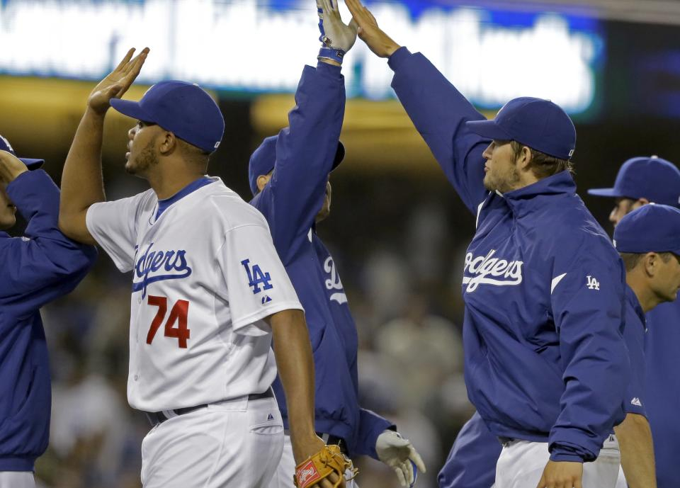 Los Angeles Dodgers closer Kenley Jansen, left, and starter Clayton Kershaw, right, celebrate with teammates after the final out against the Washington Nationals in a baseball game in Los Angeles Tuesday, May 14, 2013. Kershaw recorded 11 strikeouts and Jansen got the save as the Dodgers won, 2-0. (AP Photo/Reed Saxon)