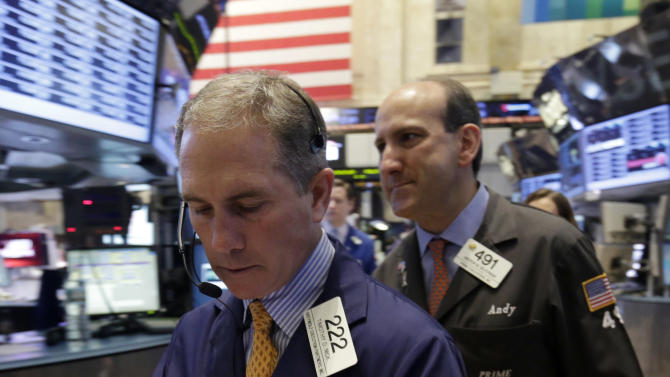 Trader Timothy Nick, left, uses his handheld device as he works on the floor of the New York Stock Exchange Thursday, April 11, 2013.  Stock indexes are little changed in early trading on Wall Street after three days of gains. (AP Photo/Richard Drew)