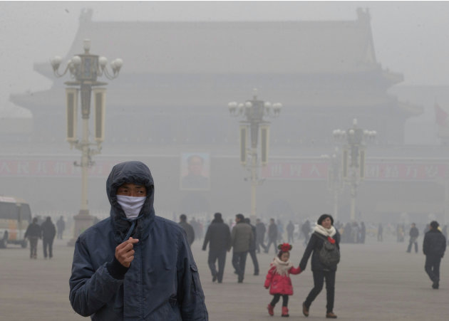 A man wears a mask on Tiananmen Square in thick haze in Beijing Tuesday, Jan. 29, 2013. Extremely high pollution levels shrouded eastern China for the second time in about two weeks Tuesday, forcing a
