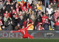Liverpool's Luis Suarez celebrates scoring against Tottenham Hotspur during their English Premier League soccer match at Anfield in Liverpool, northern England, March 10, 2013. REUTERS/Phil Noble