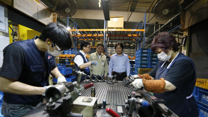 In this July 18, 2012 photo, masked employees work as Shin Cheol-soo, standing at right in the background, chief executive of ENA Industry, tours his company's assembly line in Gyeongsan, south of Seoul, South Korea. Shin no longer sees his future in the United States. The South Korean businessman supplied components to American automakers for a decade. But this year, he uprooted his family from Detroit and moved home to focus on selling to the new economic superpower: China. In just five years, China has surpassed the United States as a trading partner for much of the world, including U.S. allies such as South Korea and Australia, according to an Associated Press analysis of trade data. (AP Photo/Lee Jin-man)
