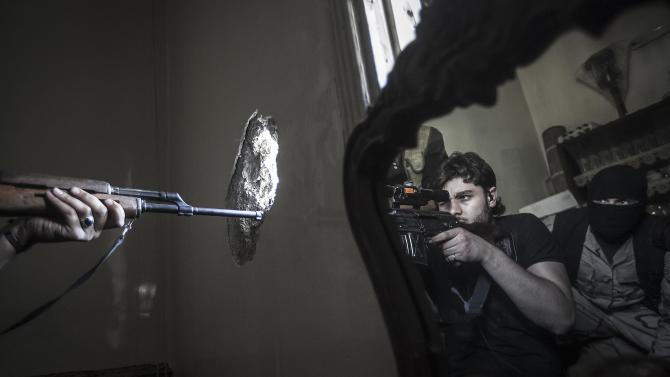 In this Monday, Oct. 29, 2012 photo, a rebel sniper aims at a Syrian army position, seen with another rebel fighter reflected in a mirror, in a residential building in the Jedida district of Aleppo, Syria. Syrian fighter jets pounded rebel areas across the country on Monday with scores of airstrikes that anti-regime activists called the most widespread bombing in a single day since Syria's troubles started 19 months ago. (AP Photo/Narciso Contreras).