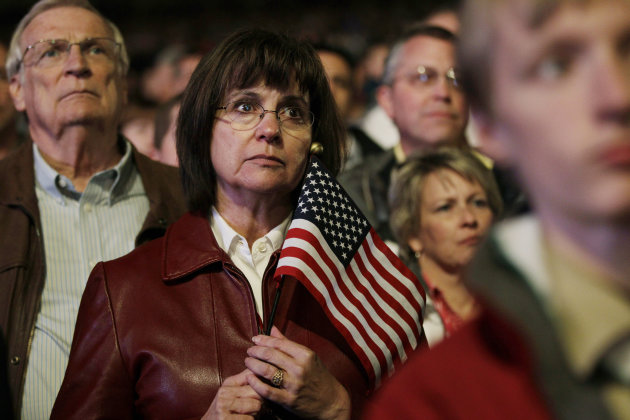 A woman holds a U.S. flag as she and others listen to a speech by Republican presidential candidate, former Massachusetts Gov. Mitt Romney, during a campaign rally in Greenwood Village, Colo. in south Denver on Saturday, Nov. 3, 2012. (AP Photo/Brennan Linsley)