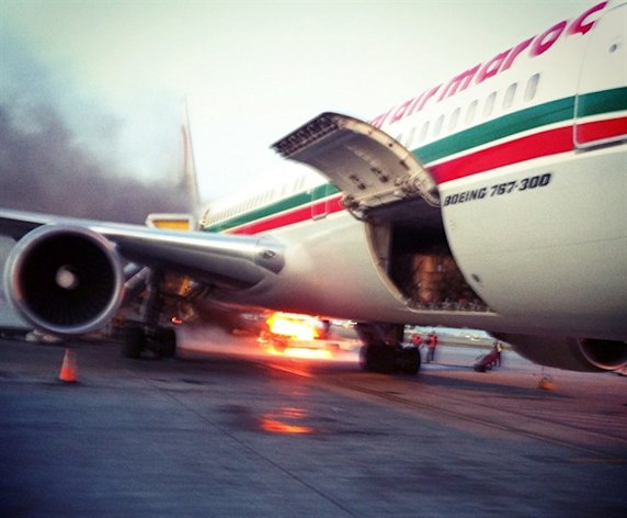 Fire burns on a bagage belt on the tarmac next to a Royal Air Maroc plane in Montreal on Monday November 4, 2013. THE CANADIAN PRESS/Olivier Lebrun