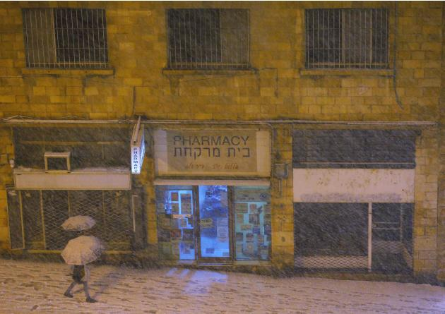 Pedestrians walk through the falling snow in Jerusalem