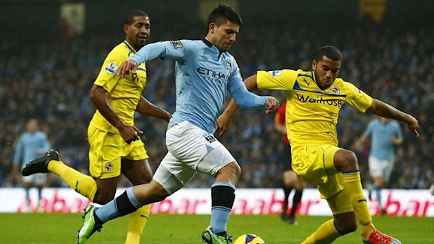 Manchester City's Sergio Aguero (C) is challenged by Reading's Adrian Mariappa during their English Premier League soccer match at The Etihad stadium in Manchester, northern England, December 22, 2012 (Reuters)