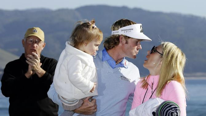 Brandt Snedeker, holding daughter Lilly, leans in to kiss his wife Mandy, who is holding son Austin, on the 18th green of the Pebble Beach Golf Links after winning the AT&T Pebble Beach Pro-Am golf tournament, Sunday, Feb. 10, 2013, in Pebble Beach, Calif. Snedeker won the tournament after shooting a 7-under 65. At left, Snedeker's playing partner Toby S. Wilt applauds. (AP Photo/Eric Risberg)