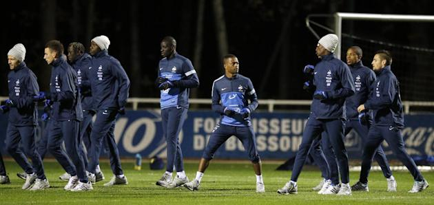 France's soccer player Patrice Evra, center, runs amid players during a training session at Clairefontaine training center, south of Paris, Monday, Nov. 11, 2013, ahead of their 2014 World Cup qualify