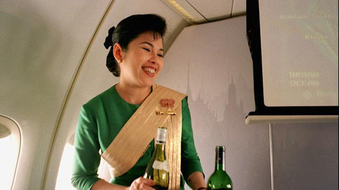 FILE - In this Dec. 14, 1996, file photo, a Thai Airways International airline flight attendant offers a passenger a selection of wine during a flight from Singapore to Bangkok. Airlines have found a way to take the edge off the stress of flying and make a few extra bucks along the way: fancy new cocktails, craft beers and elegant wines. (AP Photo/Richard Vogel)