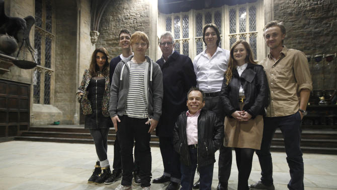 """Actors from the Harry Potter movie series, from left Natalia Tena, Oliver Phelps, Rupert Grint, Mark Williams, Warwick Davis, James Phelps, Bonnie Wright, and Tom Felton, poses for photographs at the 'Great Hall' one of the sets of the movies during a tour in Watford, north of London, Wednesday Oct. 12, 2011. This collection of sheds and sound stages, a former aerodrome near London is where the eight films were shot over almost a decade, and soon they will be home to the official """"Making of Harry Potter"""" studio tour. With more than five months to go until the site's March 31, 2012 opening, tickets go on sale Thursday Oct. 13, 2011. The eight Potter films made here between 2001 and 2010 were a mini-industry, employing both the cream of Britain's acting talent and hundreds of craftspeople and technicians. The tour will show off the skill and craftsmanship that went into the spectacle. (AP Photo/Lefteris Pitarakis)"""