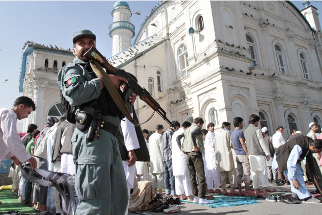 An Afghan policeman stands guard outside  Shah-e- Dushamshera's mosque where Afghans offer the Eid al-Fitr's prayers that marks the end of holy fasting month of Ramadan in Kabul, Afghanistan, Sunday,