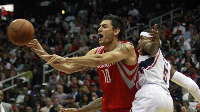Houston Rockets small forward Carlos Delfino (10) passes as Atlanta Hawks small forward Josh Smith (5) defends in the second half of an NBA basketball game on Friday, Nov. 2, 2012, in Atlanta. Houston won 109-102.  (AP Photo/John Bazemore)