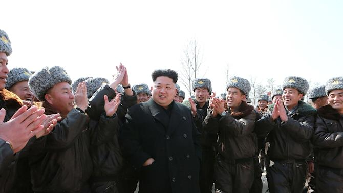This photo taken on March 2, 2015 and released by North Korea's official Korean Central News Agency on March 3, 2015 shows North Korean leader Kim Jong-Un (C) welcomed by soldiers on tree-planting at an unknown location