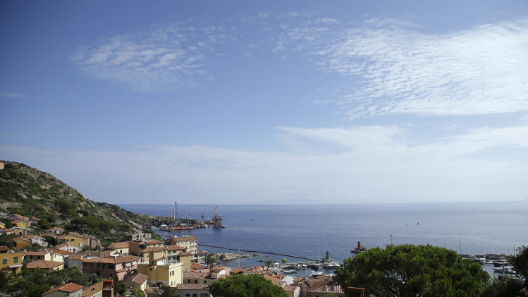 The empty platform used for the removal operations of the Costa Concordia cruise ship is seen at left, on the Tuscan island of Isola del Giglio, Italy, Thursday, July 24, 2014. The Costa Concordia left the tiny Italian island on Wednesday for Genoa's port, where it will be scrapped. On Jan. 13, 2012 it hit a reef and capsized, killing 32 people. (AP Photo/Gregorio Borgia)