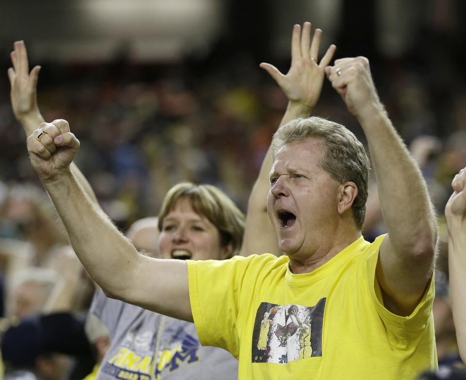 Michigan fans celebrate after the second half of the NCAA Final Four tournament college basketball semifinal game against Syracuse Saturday, April 6, 2013, in Atlanta. Michigan  won 61-56. (AP Photo/Charlie Neibergall)