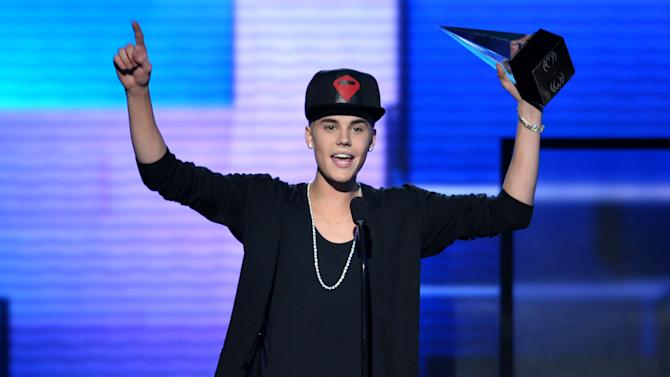 """FILE - In this Nov. 18, 2012 file photo, Justin Bieber accepts the award for favorite album - pop/rock for """"Believe"""" at the 40th Anniversary American Music Awards, in Los Angeles. Bieber is one of several stars whose homes have been targeted by pranksters who place fake 911calls to try to draw out large police responses in a hoax known as swatting. The rash of calls against celebrities is taxing police resources and prompted two California lawmakers to propose stiffer penalties for convicted swatters. (Photo by John Shearer/Invision/AP, File)"""