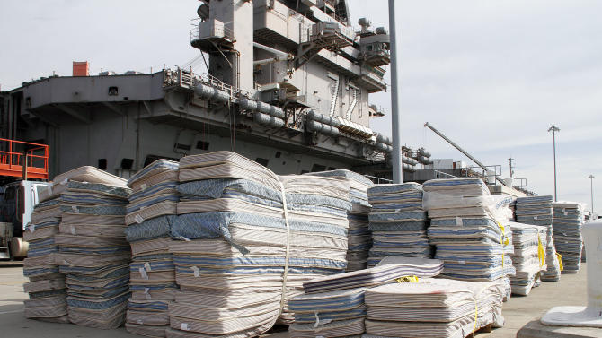 In this Oct. 15, 2012 photo provided by the U.S. Navy,mattresses from the USS Abraham Lincoln to be recycled await transport on Pier 11 Naval Station in Norfolk, Va.  The mattresses from two Virginia-based aircraft carriers and an amphibious transport dock are having their parts recycled by a South Carolina company this year for other uses. In all, the Navy plans to recycle 13,000 mattresses from the USS Enterprise, USS Abraham Lincoln and USS Mesa Verde as part of a pilot program run by Naval Facilities Engineering Command Mid-Atlantic's Integrated Solid Waste. (AP Photo/U.S. Navy, John Land) Recycling