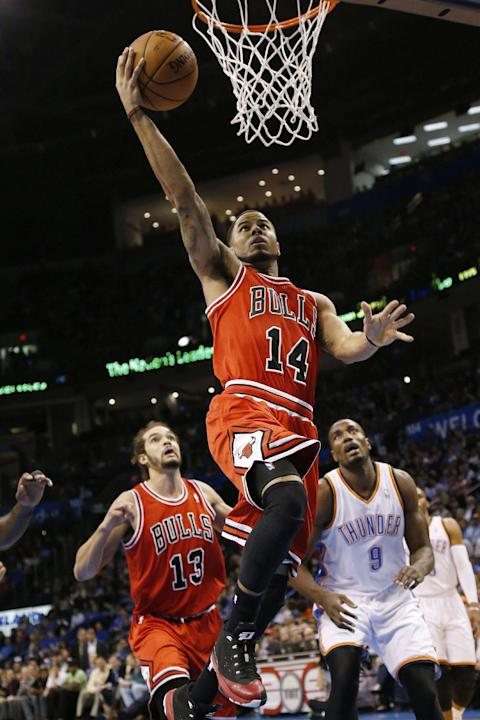 Chicago Bulls guard D.J. Augustin (14) shoots in front of Oklahoma City Thunder forward Serge Ibaka (9) and Bulls center Joakim Noah (13) during the first quarter of an NBA basketball game in Oklahoma