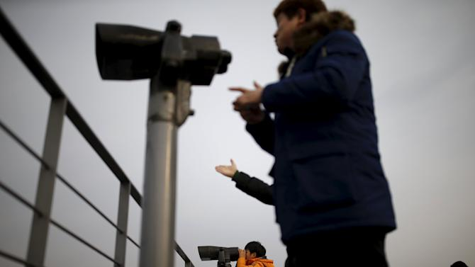 People look to the north through binoculars from an observatory platform near the demilitarized zone separating the two Koreas in Paju
