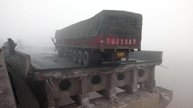 CORRECTS DATE - In this photo provided by China's Xinhua News Agency, a truck sits on the expressway bridge which partially collapsed due to an explosion in Mianchi County, Sanmenxia, central China's Henan Province, Friday, Feb. 1, 2013.  Fireworks for Lunar New Year celebrations exploded on a truck in central China, destroying part of an elevated highway Friday and sending vehicles plummeting 30 meters (about 100 feet) to the ground. (AP Photo/Xinhua, Xiao Meng) NO SALES