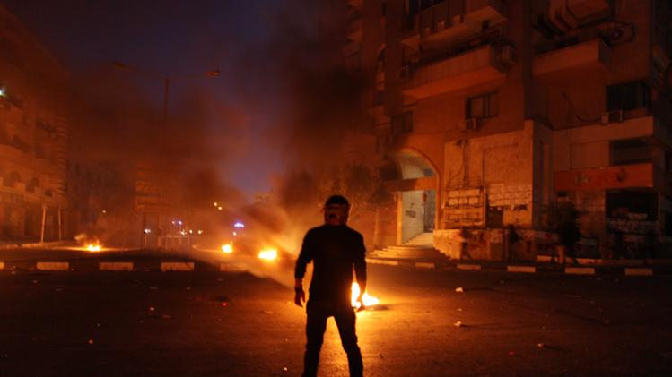 Egyptian protesters set tires on fire during clashes between supporters and opponents of Egypt's powerful Muslim Brotherhood near the Islamist group's headquarters in Cairo, Egypt  Friday, March 22, 2013. (AP Photo/Khalil Hamra)