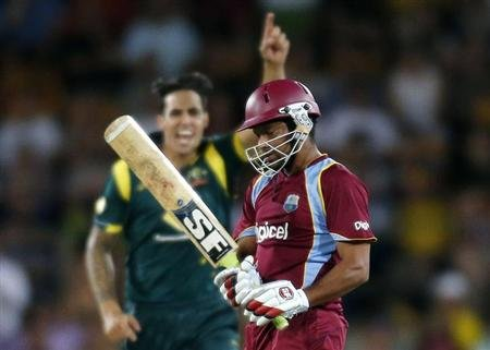West Indies' Sarwan reacts as Australia's Johnson celebrates bowling him out during their one-day international cricket match at Manuka Oval in Canberra