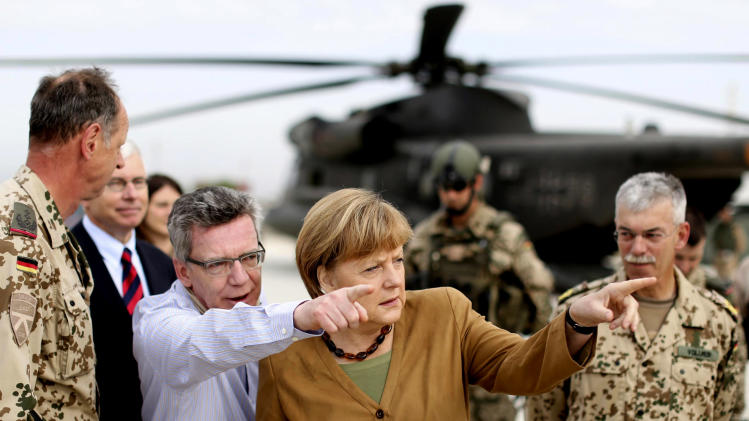 German Chancellor Angela Merkel, center, and German Defense Minister Thomas de Maiziere, left, gesture as they arrive to Kunduz, Afghanistan, Friday, May 10, 2013. Germany's Chancellor Angela Merkel made a surprise visit to northern Afghanistan to visit her troops less than two weeks after insurgents killed a German special forces soldier and wounded a second, a military spokesman said. Germany is the only NATO nation that is committed to leaving troops in Afghanistan after the coalition completes its scheduled pullout of combat forces next year. The U.S. is likely to deploy several thousand troops if the Afghan government provides them legal protection. (AP Photo/DPA/Kay Nietfeld)
