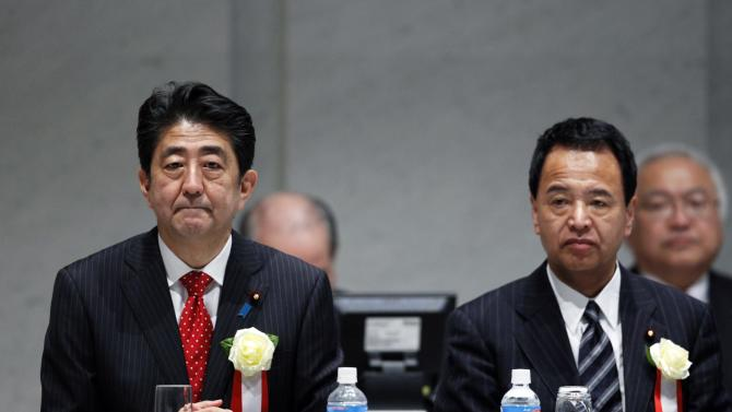 Japan's Prime Minister Abe sits with Japan's Economics Minister Amari during a year end meeting at Japan Business Federation in Tokyo