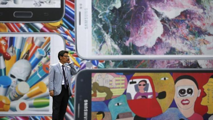 A man uses his mobile phone in front of a giant advertisement promoting Samsung Electronics' new Galaxy S5 smartphone, at an art hall in central Seoul
