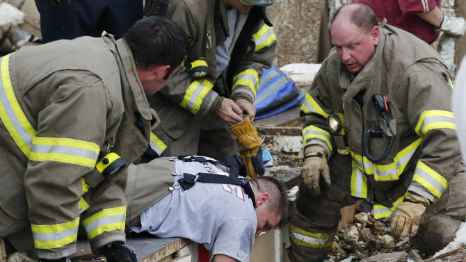 Rescue workers dig through the rubble of a collapsed wall at the Plaza Tower Elementary School to free trapped students in Moore, Okla., following a tornado Monday, May 20, 2013. A tornado as much as a mile (1.6 kilometers) wide with winds up to 200 mph (320 kph) roared through the Oklahoma City suburbs Monday, flattening entire neighborhoods, setting buildings on fire and landing a direct blow on an elementary school. (AP Photo/Sue Ogrocki)