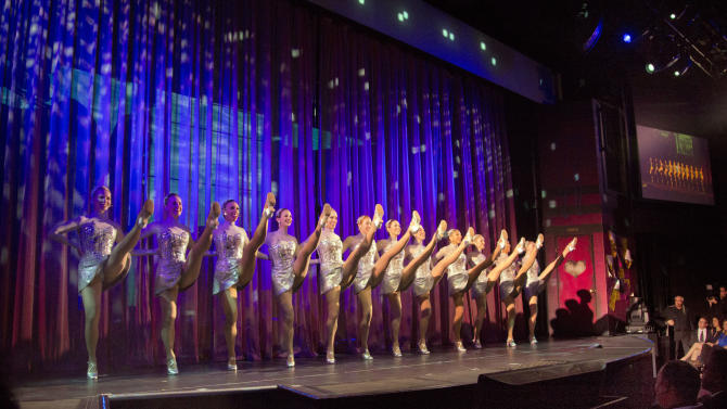 The Rockettes, best-known for dancing at the Radio City Christmas Spectacular, do their signature kick line during christening ceremonies aboard the Norwegian Cruise Line's new ship, Norwegian Breakaway, in New York, Wednesday, May 8, 2013. The ship has a colorful mural on the exterior hull design by pop artist Peter Max featuring the city skyline and the Statue of Liberty. (AP Photo/Richard Drew)